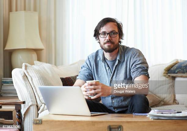Portrait of man sitting on sofa with laptop and hot drink.