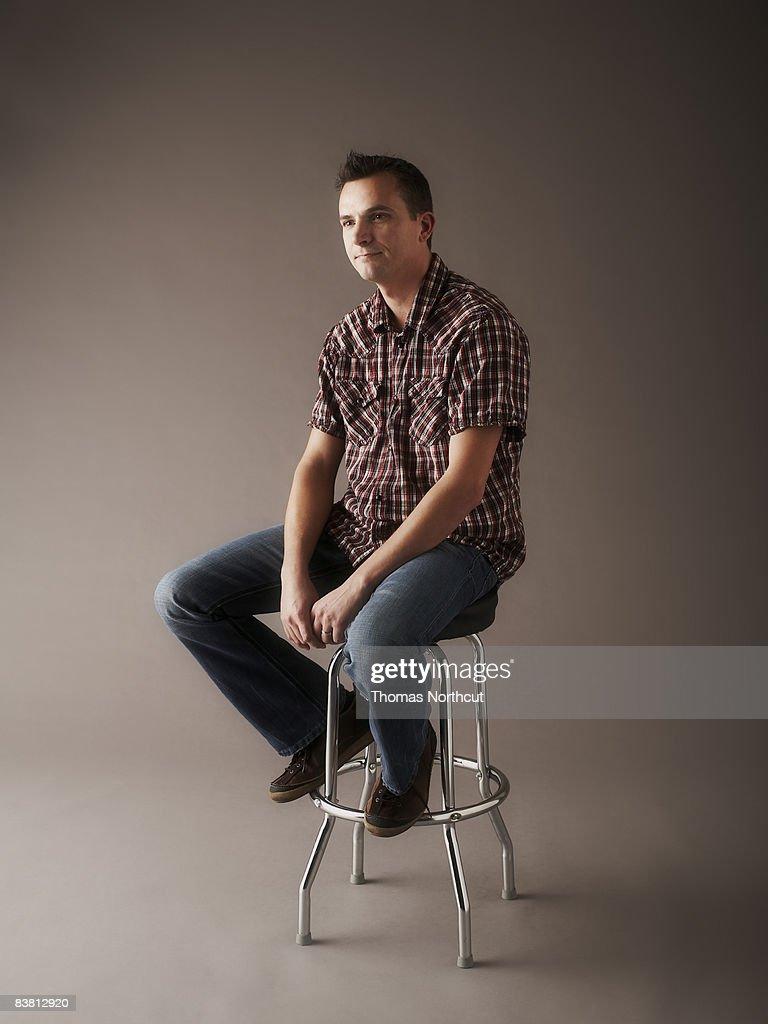 Portrait of man sitting on stool : Stock Photo