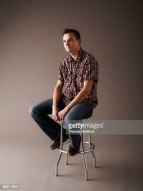 Portrait of man sitting on stool
