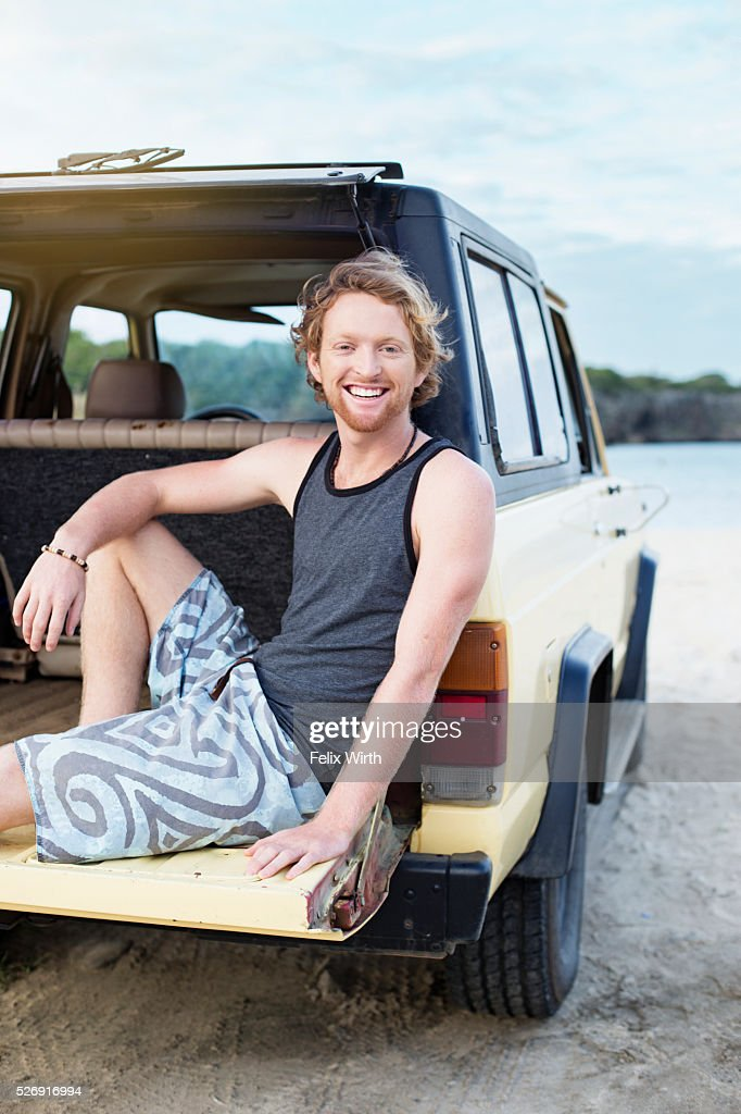 Portrait of man sitting on tailgate of truck : Photo