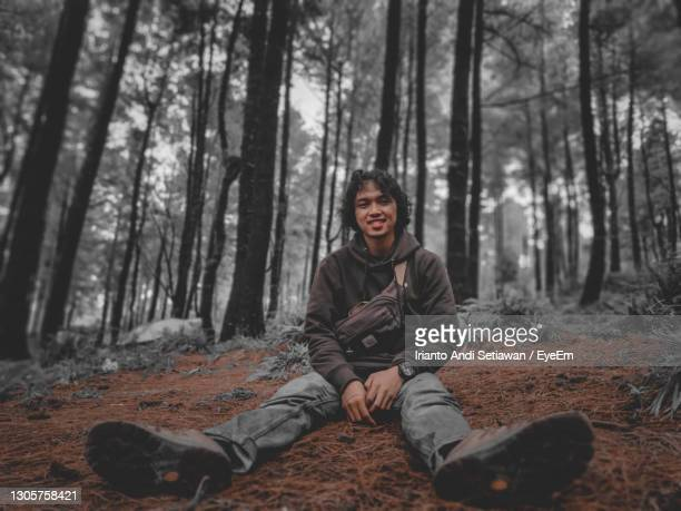 portrait of man sitting on tree trunk in forest - indonesia stock pictures, royalty-free photos & images