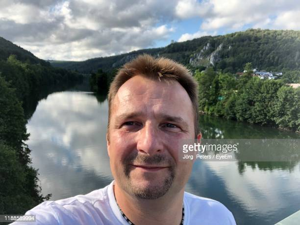 "portrait of man smiling against lake - ""jörg peters"" stock-fotos und bilder"