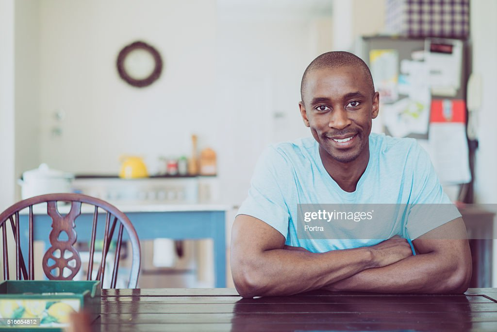 Portrait of man smiling at table in kitchen : Stock Photo