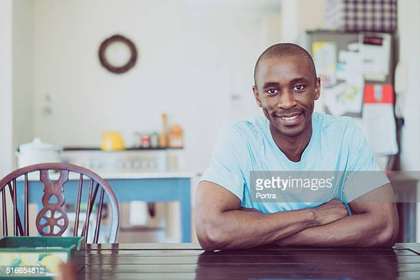 Portrait of man smiling at table in kitchen