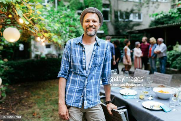 portrait of man smiling during family bbq - vollbart stock-fotos und bilder