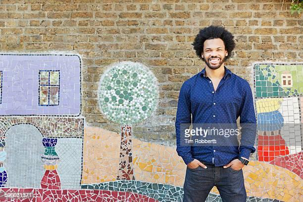 portrait of man smiling in front of art wall. - buntes hemd stock-fotos und bilder