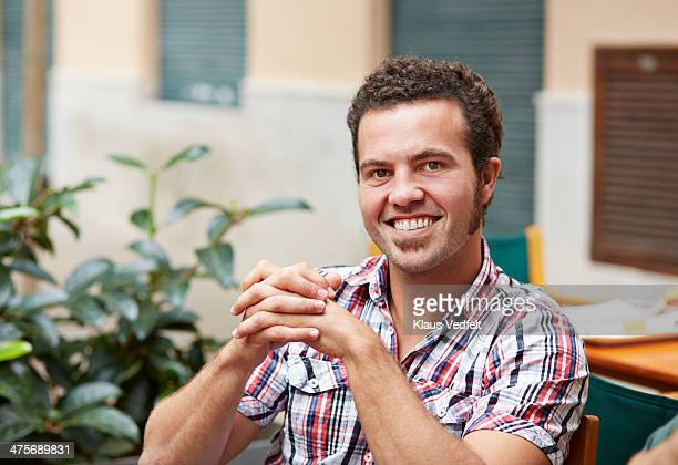 portrait of man smiling, sitting at café - klaus vedfelt mallorca stock pictures, royalty-free photos & images