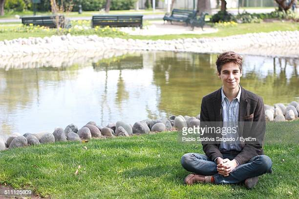 Portrait of man smiling while sitting against lake