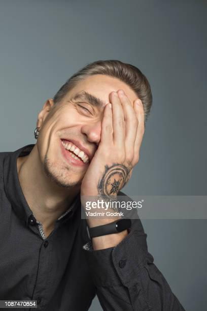 portrait of man smiling with head in hands against gray background - un seul homme photos et images de collection