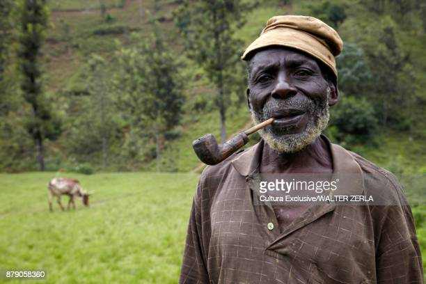 Portrait of man smoking a pipe in field, Masango, Cibitoke, Burundi, Africa
