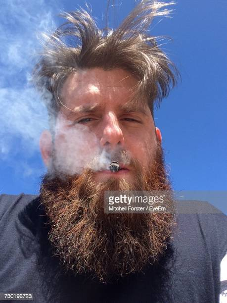 Portrait Of Man Smoking Against Sky
