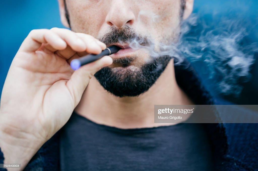 Portrait of man smoking an electronic cigarette : Stock Photo