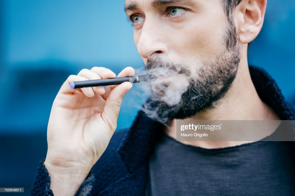 Portrait of man smoking an electronic cigarette : Stock Photo