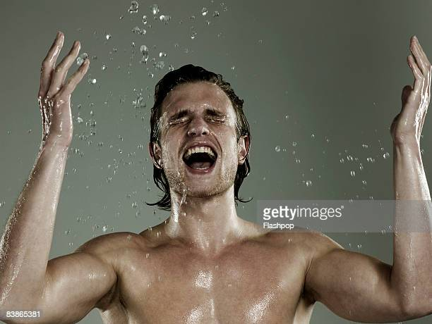 Portrait of man splashing his face with water