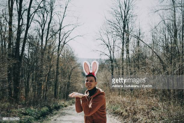 portrait of man standing against bare trees in forest - adriana duduleanu stock photos and pictures