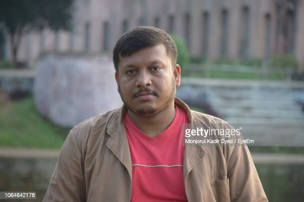 portrait of man standing against building - bangladeshi man stock photos and pictures