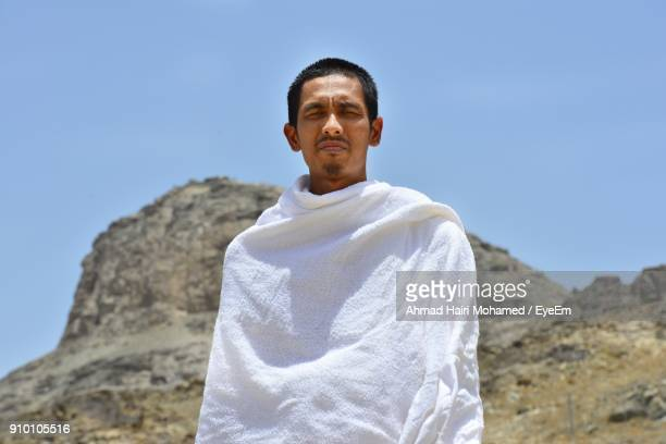 portrait of man standing against clear blue sky - pilgrimage stock pictures, royalty-free photos & images