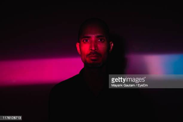 portrait of man standing against illuminated wall - lighting equipment stock pictures, royalty-free photos & images