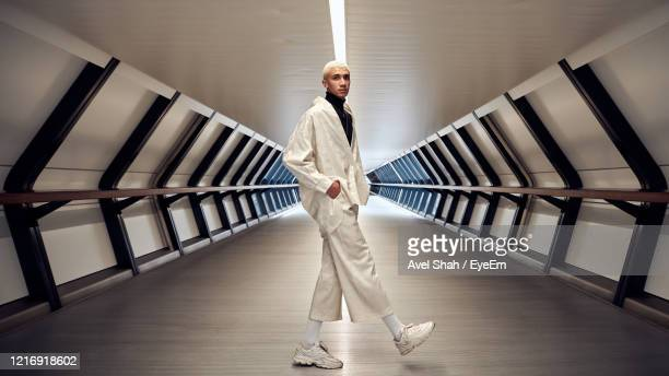portrait of man standing against railing - fashion model stock pictures, royalty-free photos & images