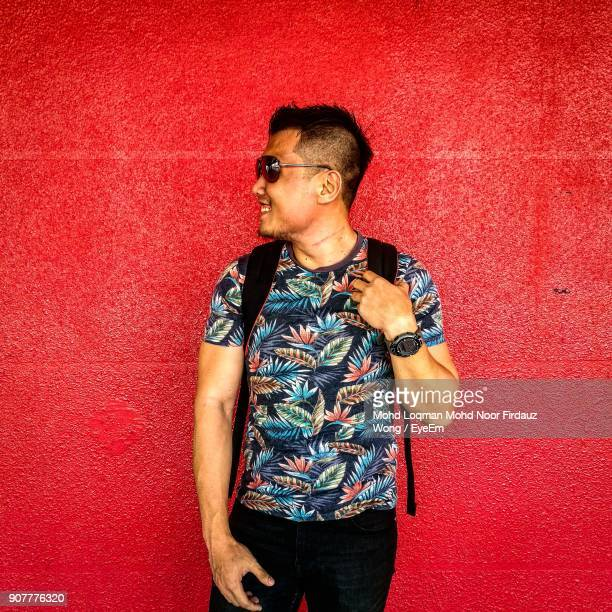 Portrait Of Man Standing Against Red Background