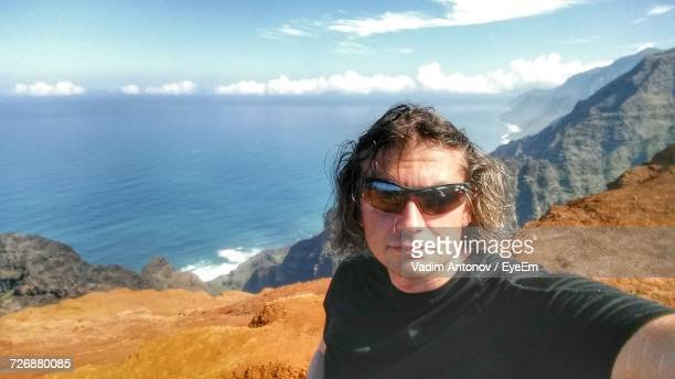portrait of man standing against sea - antonov stock pictures, royalty-free photos & images