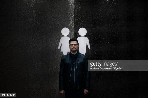 Portrait Of Man Standing Against Symbols On Wall