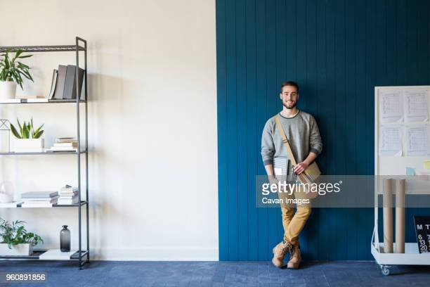 portrait of man standing against wall in classroom - leaning stock pictures, royalty-free photos & images