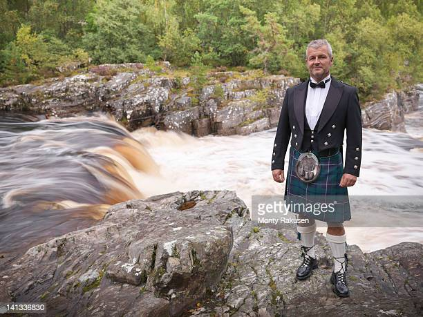portrait of man standing by flowing river in traditional scottish prince charlie outfit with douglas modern tartan - kilt stock photos and pictures