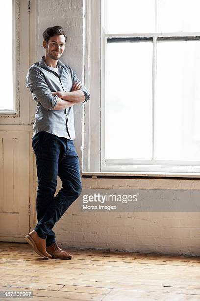 portrait of man standing by window - rolled up sleeves stock pictures, royalty-free photos & images