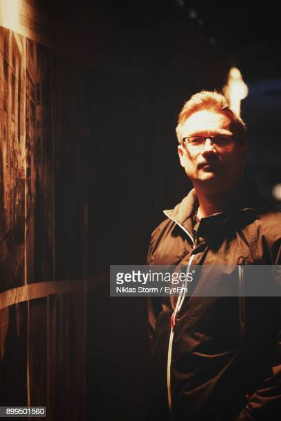 portrait of man standing by wooden wall at night - niklas storm eyeem stock photos and pictures