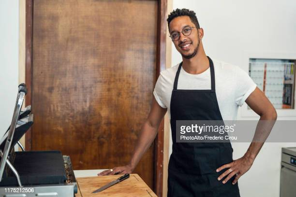 portrait of man standing in commercial kitchen - apron stock pictures, royalty-free photos & images