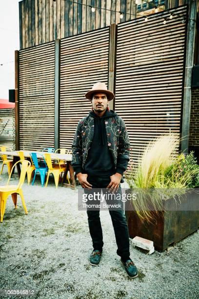 Portrait of man standing in courtyard of outdoor bar