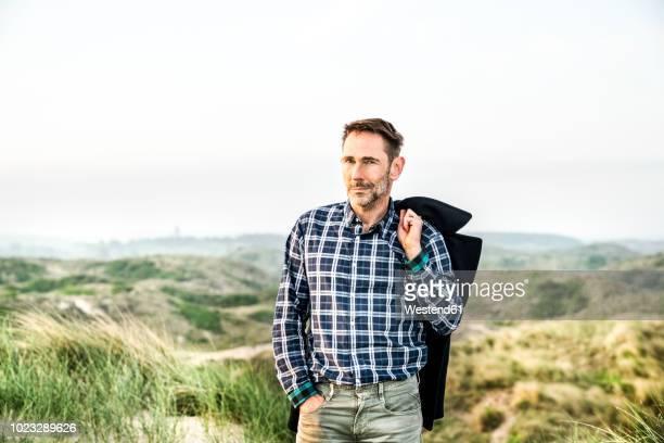 portrait of man standing in dunes - barba por fazer imagens e fotografias de stock