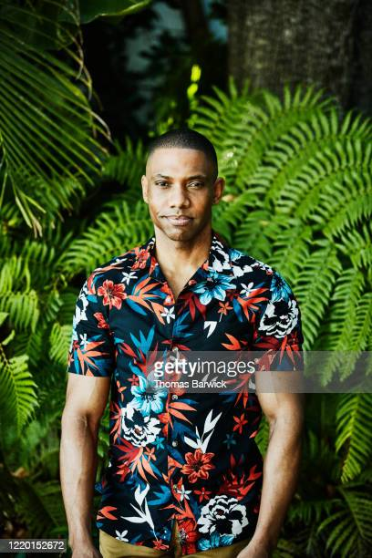 portrait of man standing in garden in tropical shirt - modern manhood stock pictures, royalty-free photos & images