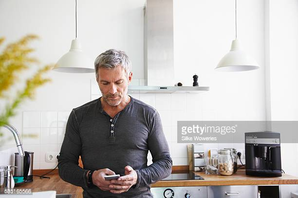 portrait of man standing in kitchen and using smartphone - da cintura para cima imagens e fotografias de stock