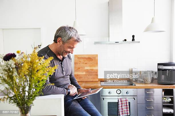 Portrait of man standing in kitchen and using tablet PC