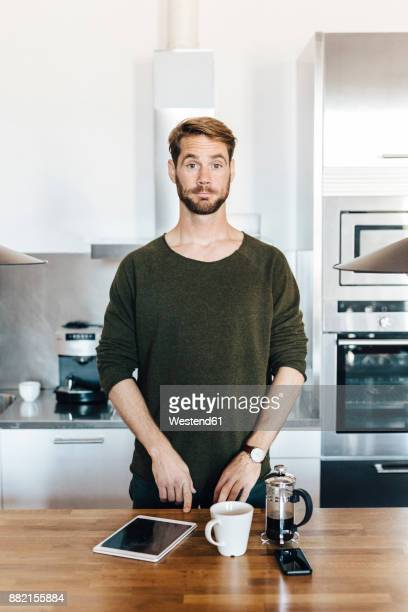 portrait of man standing in kitchen raising his eyebrows - überraschung stock-fotos und bilder