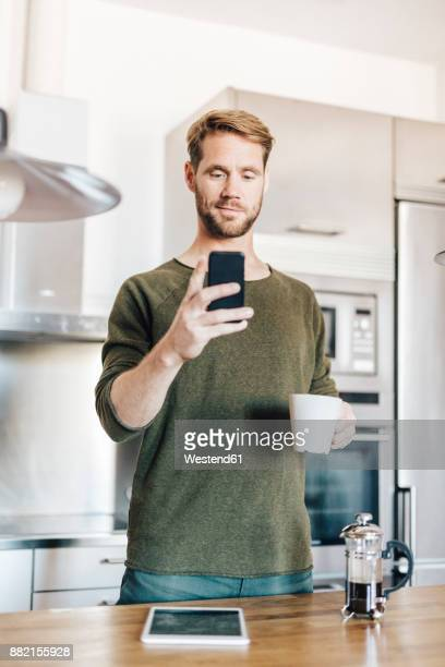 Portrait of man standing in kitchen with cup of coffee taking selfie with smartphone