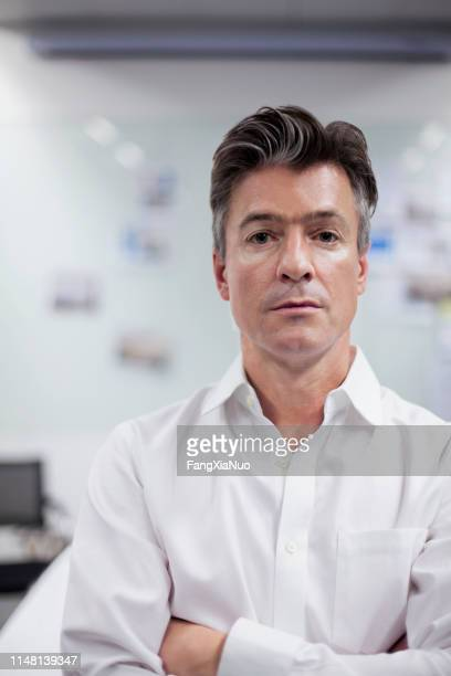 portrait of man standing in office meeting room - colletto aperto foto e immagini stock