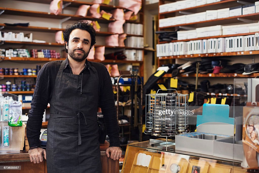 Portrait of man standing in shoe repair store : Stock Photo
