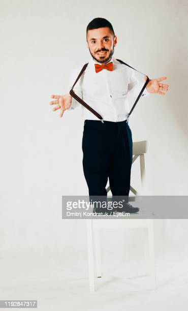 portrait of man standing on chair against white background - dwarf man stock pictures, royalty-free photos & images