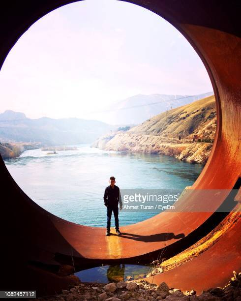 portrait of man standing on large circle pipe with river in background at dam - reservoir stock pictures, royalty-free photos & images