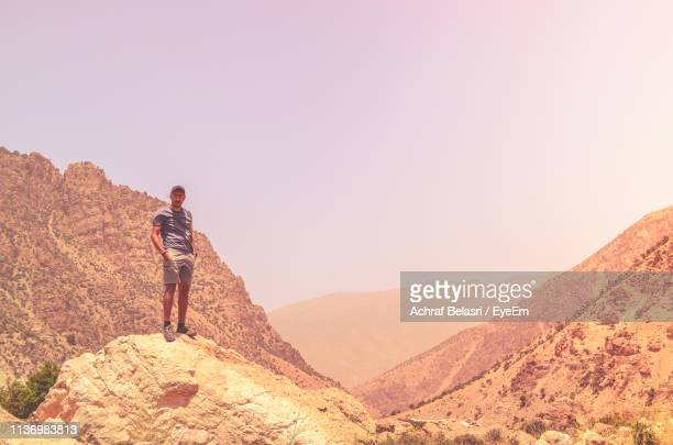 Portrait Of Man Standing On Rock Against Mountain