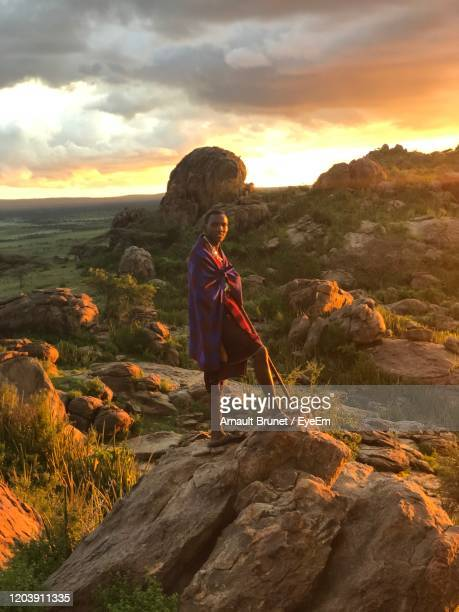 portrait of man standing on rock against sky during sunset - arnault stock pictures, royalty-free photos & images