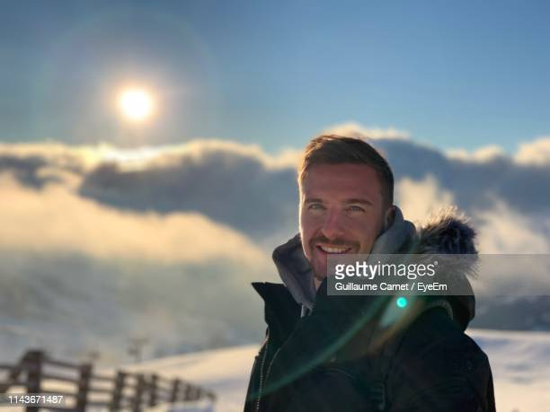 portrait of man standing on snowcapped mountain against sky - carnet stock photos and pictures
