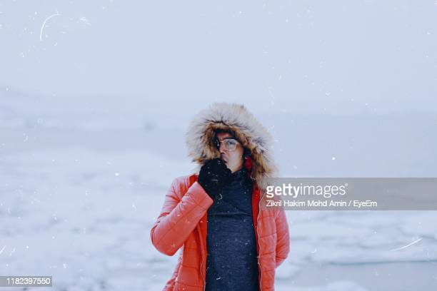 portrait of man standing on snowy land against sky - fur hat stock pictures, royalty-free photos & images