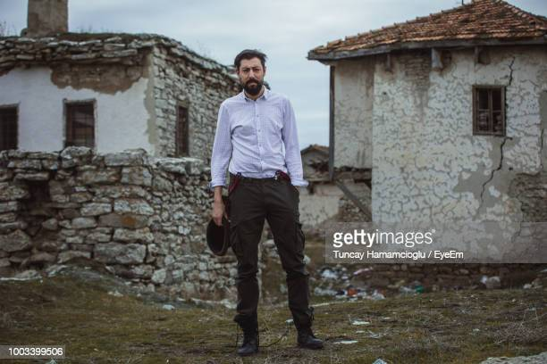 Portrait Of Man Standing Outside Old Houses Against Sky