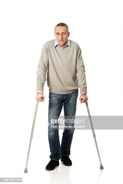 portrait of man standing with walking cane against white background - walking cane stock pictures, royalty-free photos & images