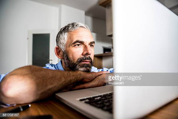 Portrait of man staring at his laptop