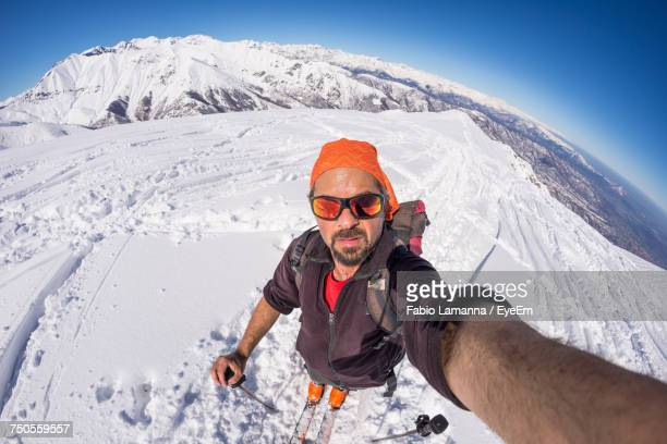 portrait of man taking selfie while standing on snowy field - wide angle stock pictures, royalty-free photos & images
